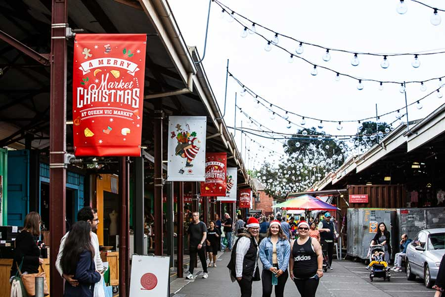 People standing in a walk way in an outdoor market wearing santa hats