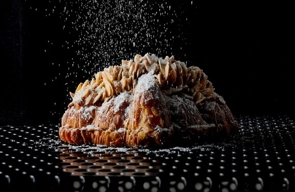 sugar falling onto a croissant pastry topped with almond flakes
