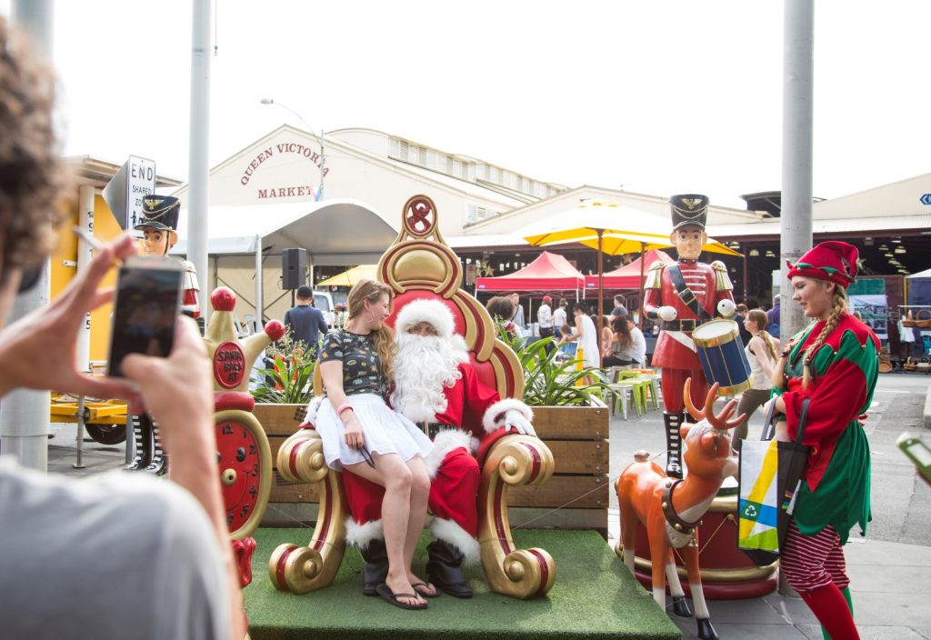 Santa Claus sitting on a throne outside, surrounded by Christmas decorations