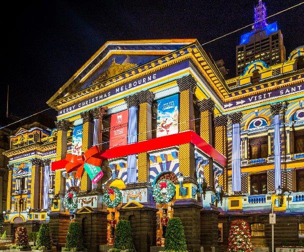 Colourful projections on Melbourne's Town Hall Building. The pillars appear empasised in yellow and other parts of building have blue projections - there's also a big red bow.