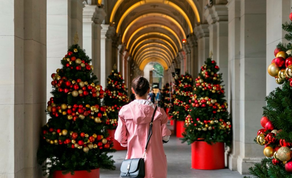 A woman walking through a series of arches lined with Christmas trees