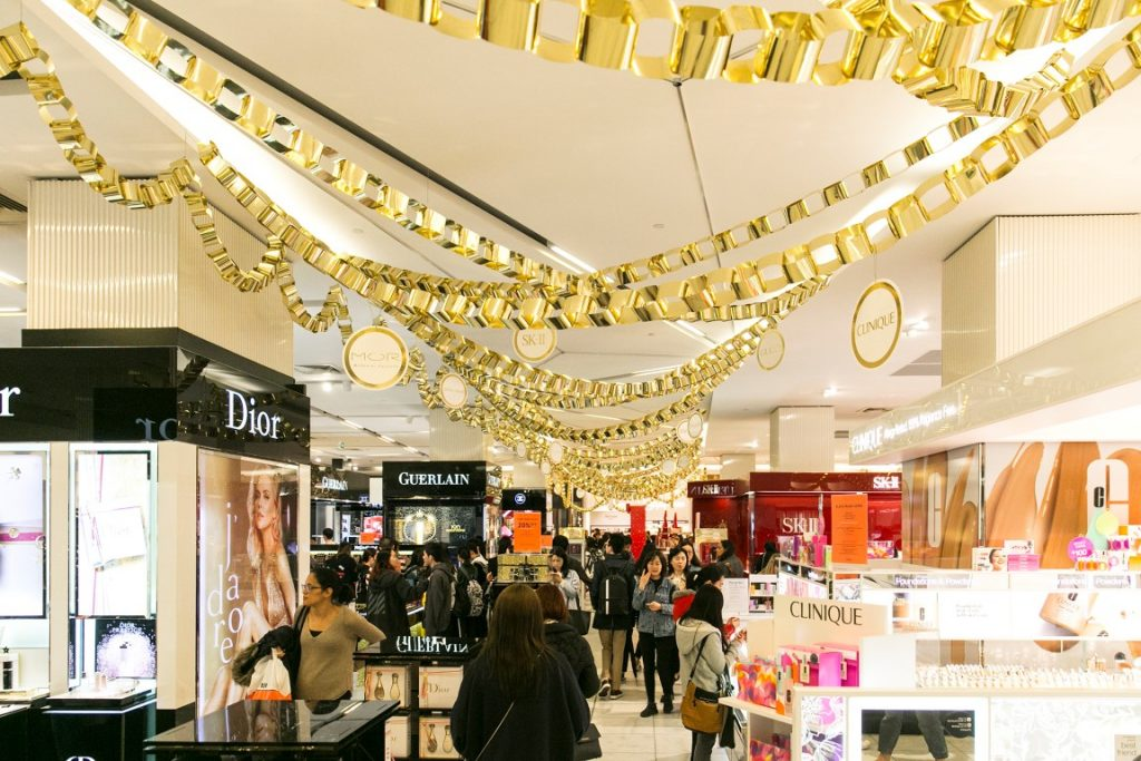 Gold decorations hanging from the ceiling in a busy department store