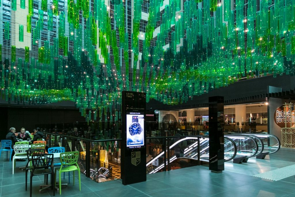 A ornate ceiling in a shopping centre made of hanging glass sculptures above an escalator