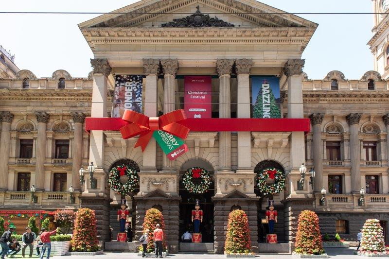 Melbourne's Town Hall decorated with nutcrackers, Christmas wreaths and a giant, red bow.