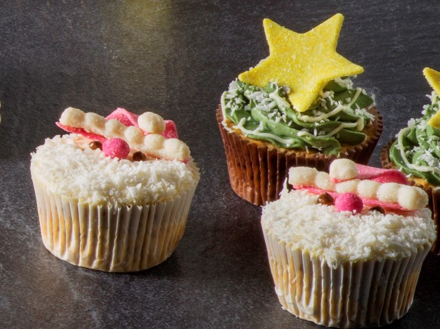 Two cupcakes in a white box. One decorated like santa and the other is decorated like a christmas tree