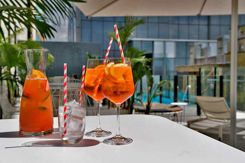A jug of gin cocktail and glasses of Aperol spritz