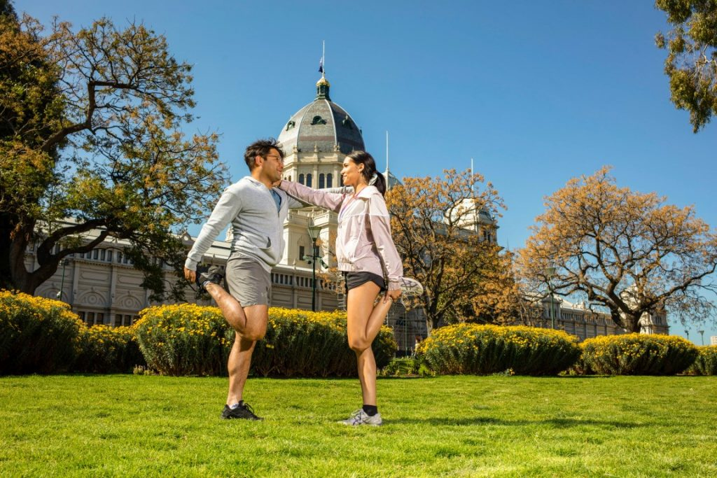 Two people wearing exercise gear warming up on a lawn in front of an old garden