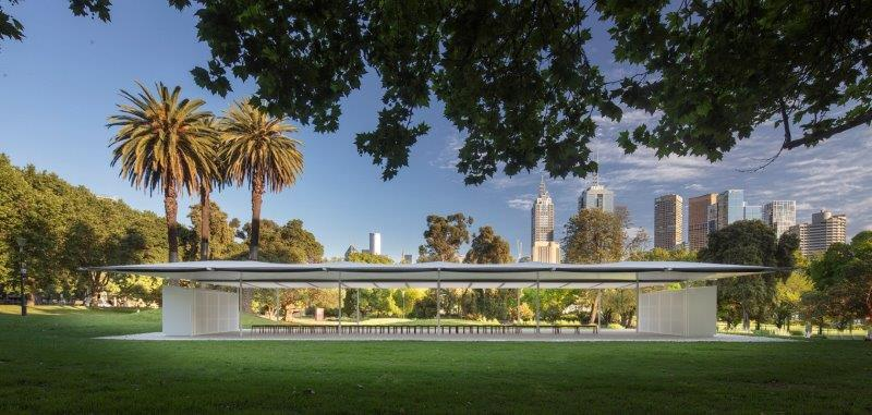 The MPavilion building with grass and trees visible in the foreground and Melbourne's CBD in the background.