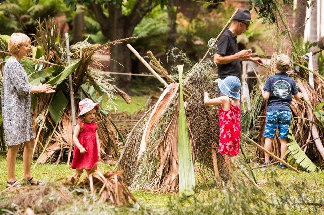A mum, dad and two little kids building a hut out of palm fronds and other found material at the Royal Botanic Gardens
