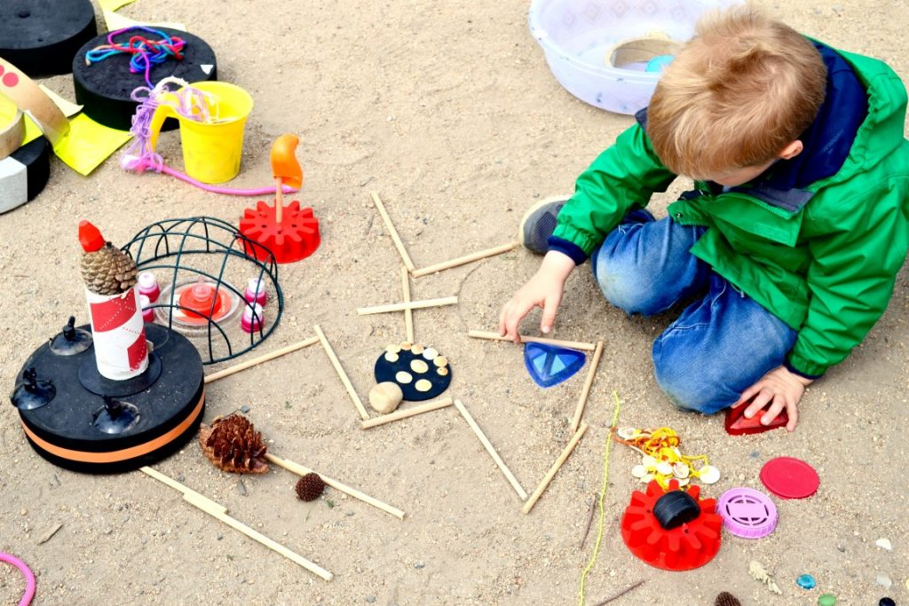 A child sitting on the floor making a picture from sticks and other items