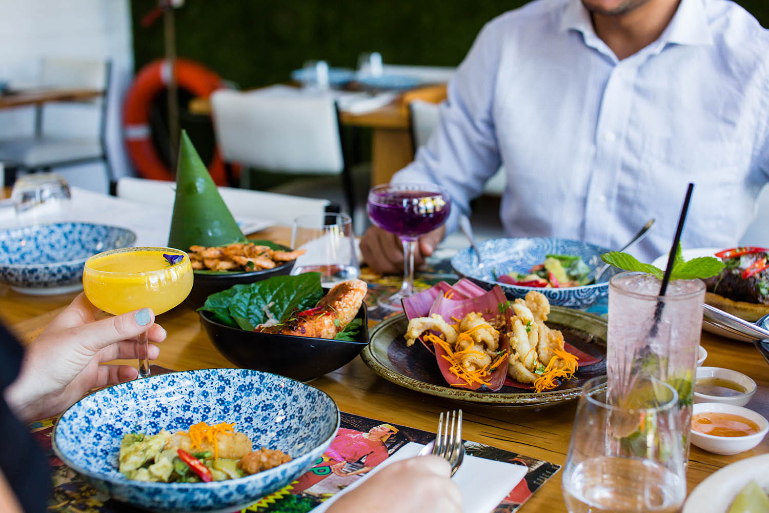 A table full of Asian food with cocktails