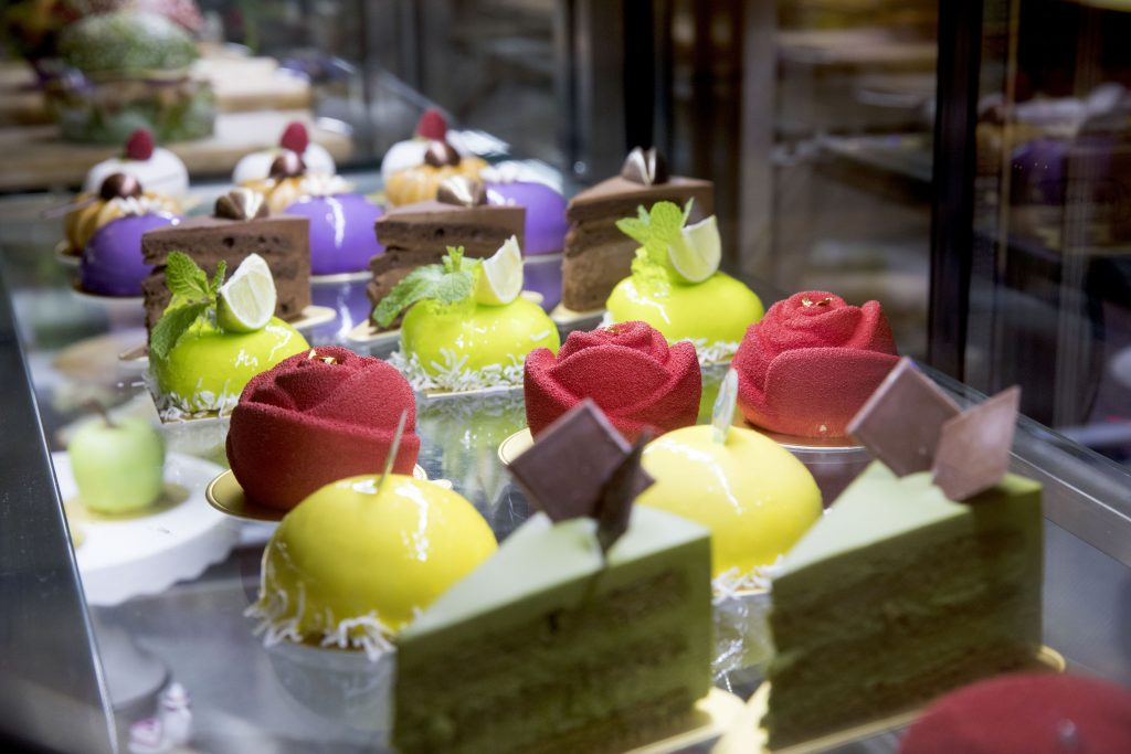 A selection of fancy cakes and parties in a display in a shop