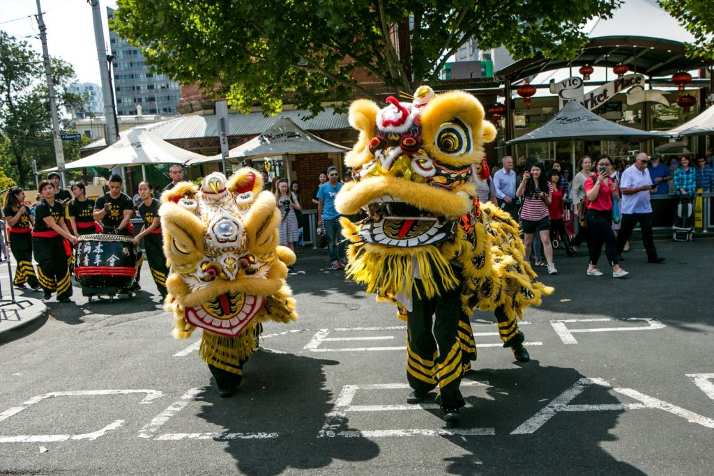 Chinese lions performing in front of a crowd at an outdoor market