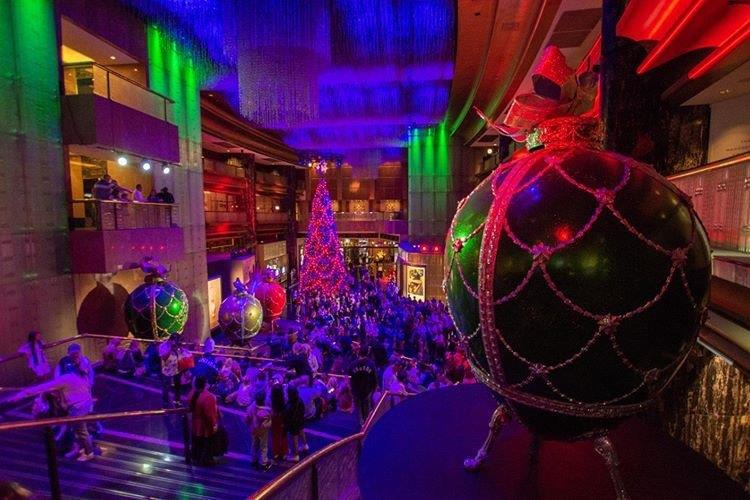 A large atrium area with festive red and green Chritsmas lights projected on to walls and huge Christmas decorations suspended from ceiling.
