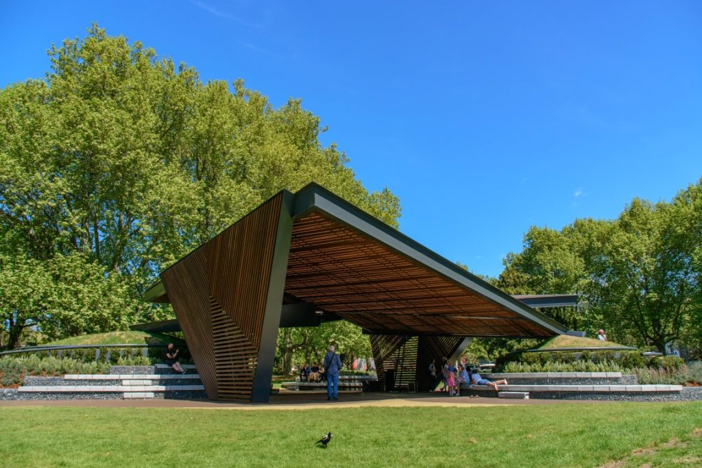 A modern structure that looks like a big outdoor shelter in a park