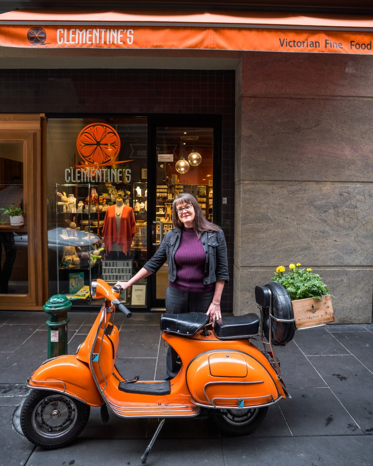 A woman standing behind a vespa in front of a shop