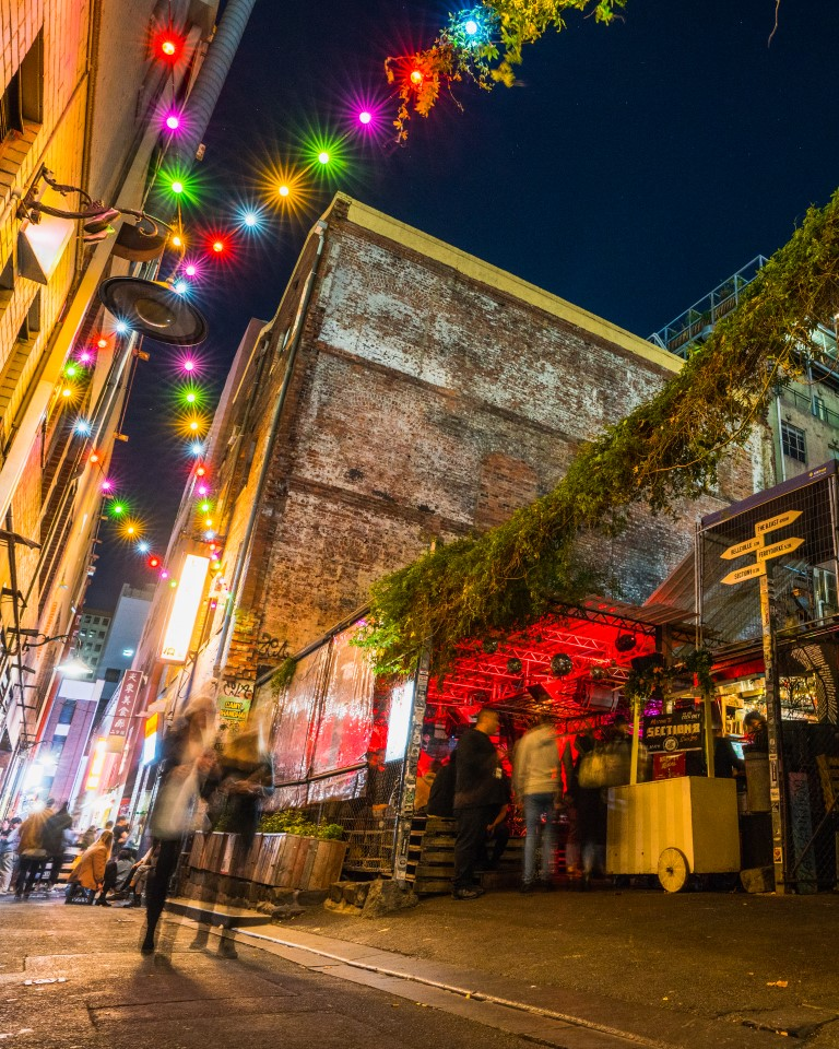 An outdoor bar in a city laneway covered in fairy lights at night