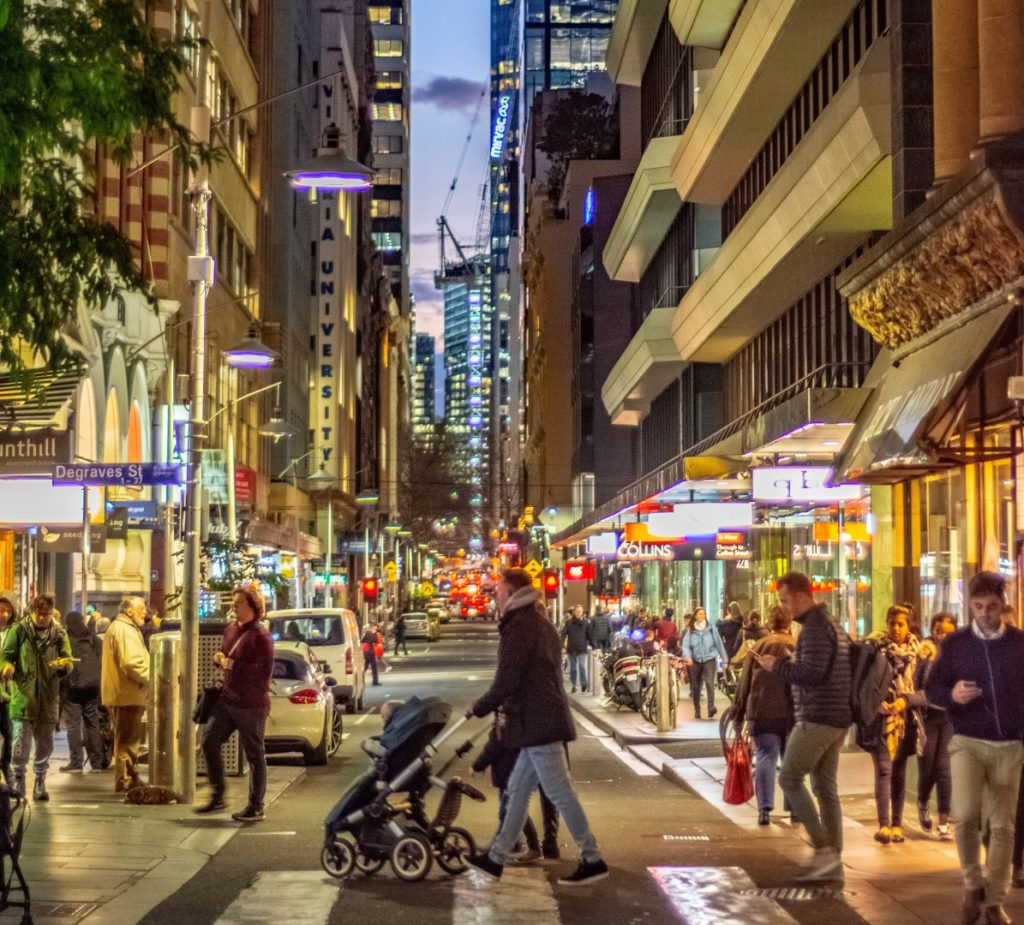 People walking along a crowded city laneway at night