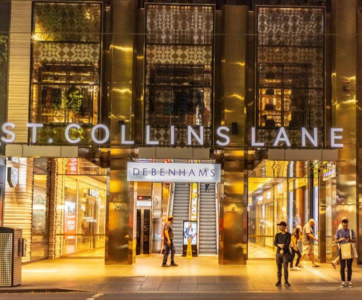 he entrance way to St. Collins Lane lit up at night time