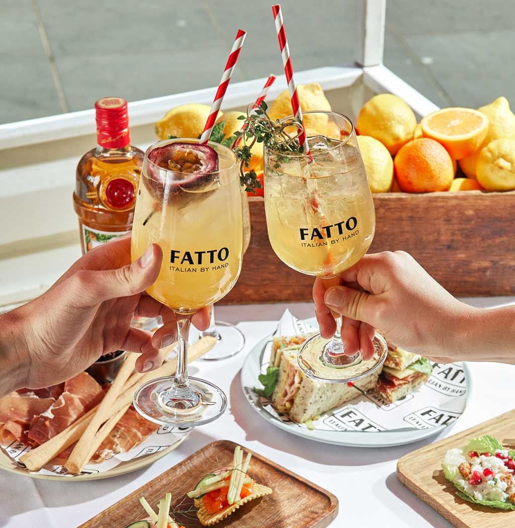 Two glasses filled with alcohol clinking together over a table of food