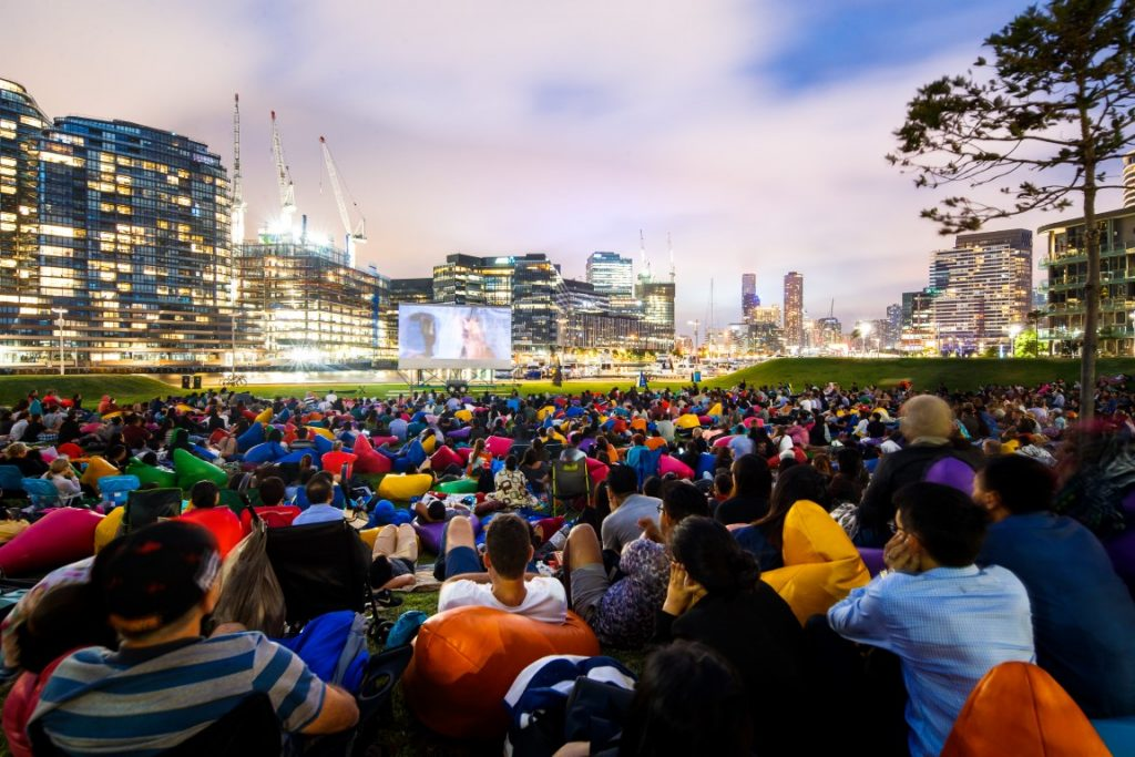A crowd of people sitting on a lawn watching a movie on a big screen with the city skyline in the background