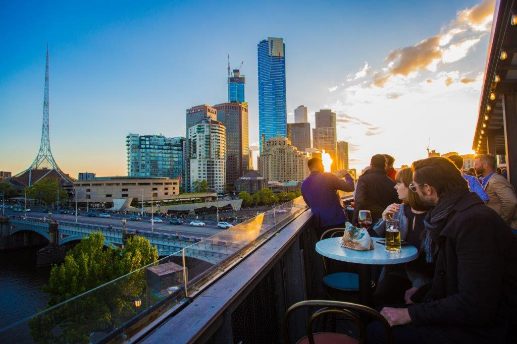 The balcony at transit bar with people sitting at tables overlooking the yarra at sunset. The art's centre is visible in the distance.