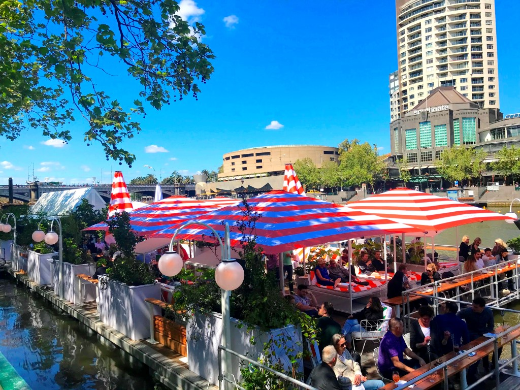 A crowd of people on a bar on a floating barge on a river.