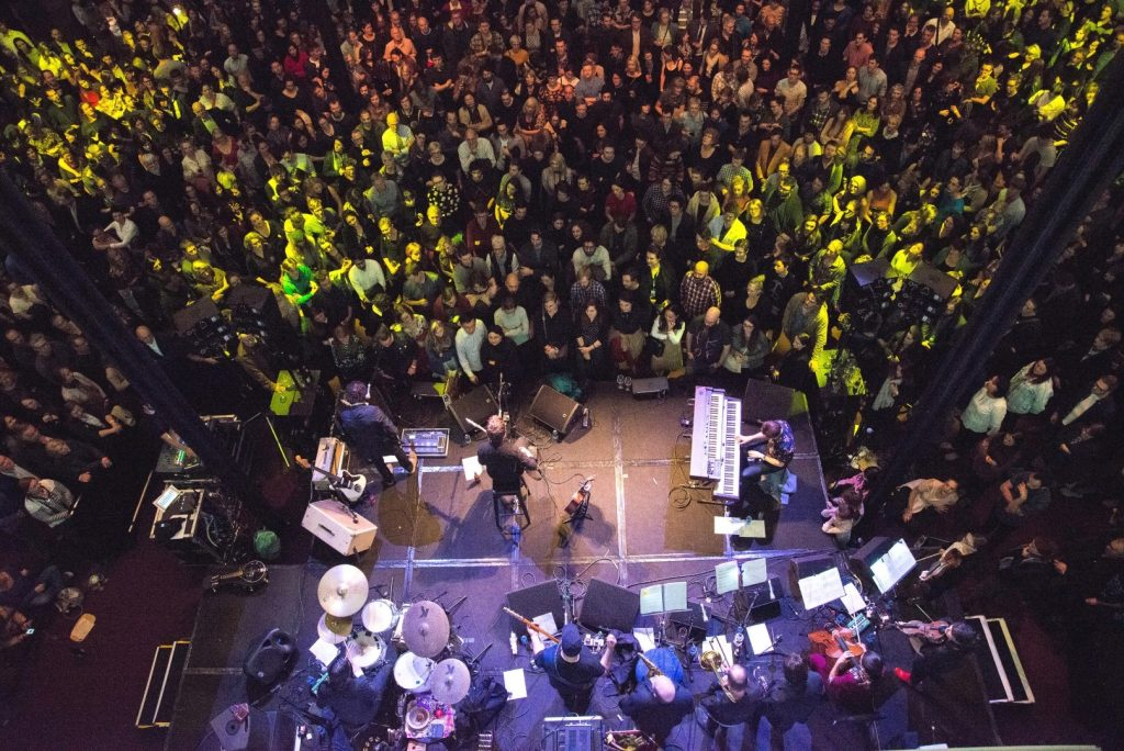 Aerial view of a crowd of people watching a band perform on a stage