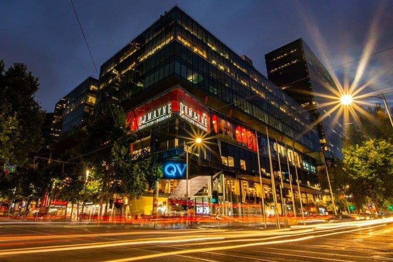 QV Melbourne shopping centre lit up at night