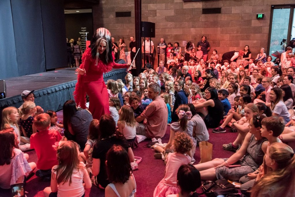 A performer giving a show in front of a crowd of adults and kids sitting down
