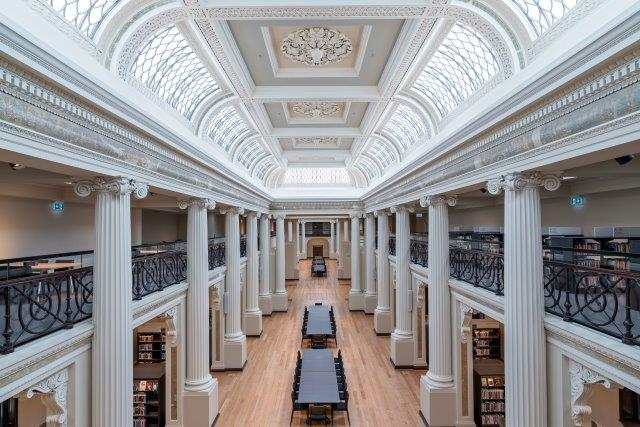 Photo showing long hall with long white archway for ceiling and and white columns along each side.