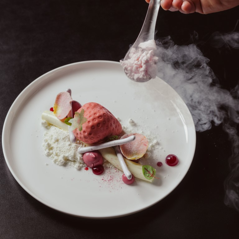 A spoon with smoke coming off it being held above a plate of sorbet and fruit