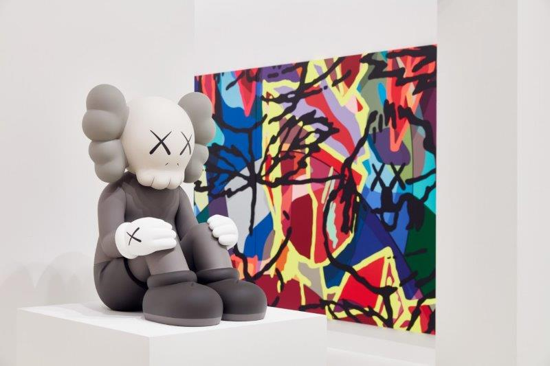 A KAWS sculpture sitting in front of a bright coloured abstract painting. The sculpture has KAWS' typical cartoon-like rounded features and a white face with oversized grey ears and black crosses for eyes.