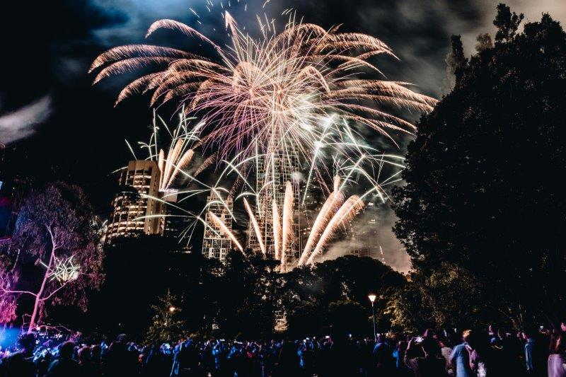 Fireworks light up the night sky with yellow pink and blue
