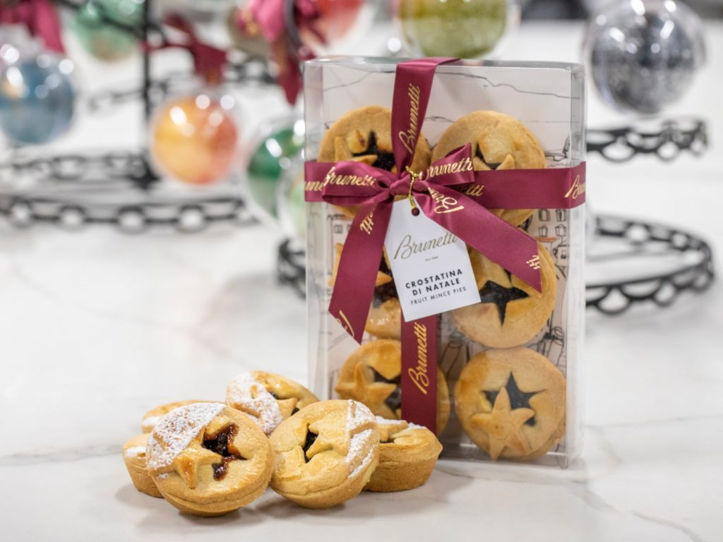 A few mince pies on a marble table with mince pies in a plastic box behind it