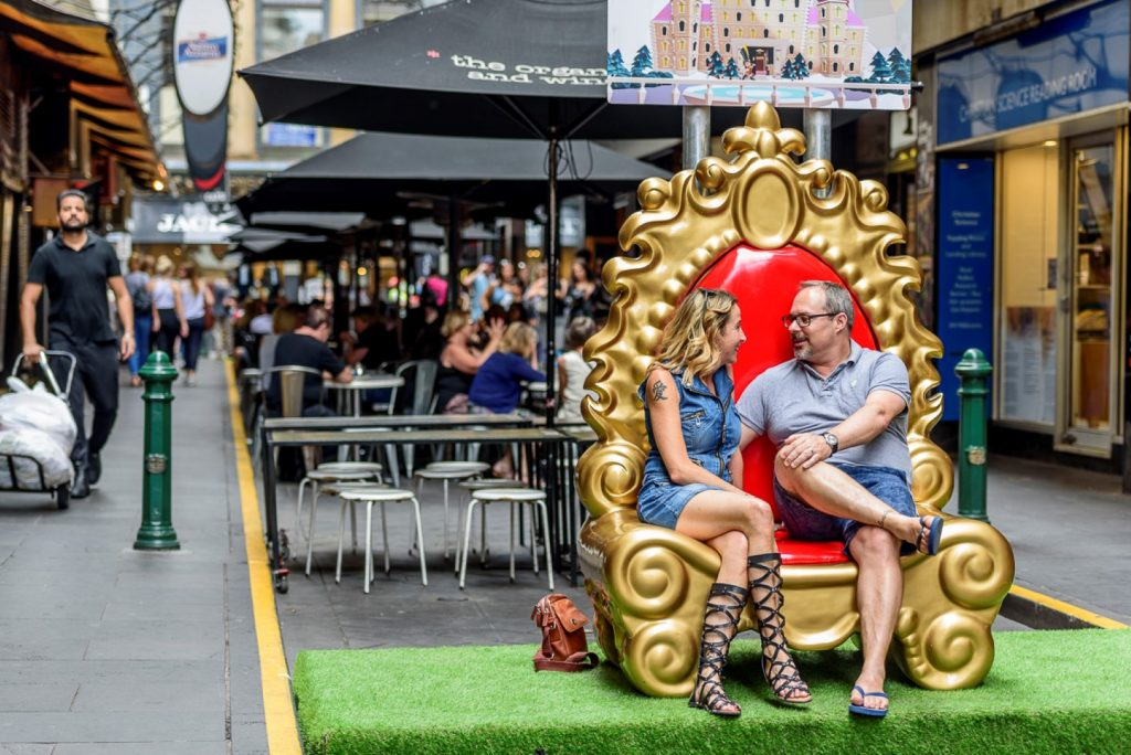 People sitting on a throne in a city laneway