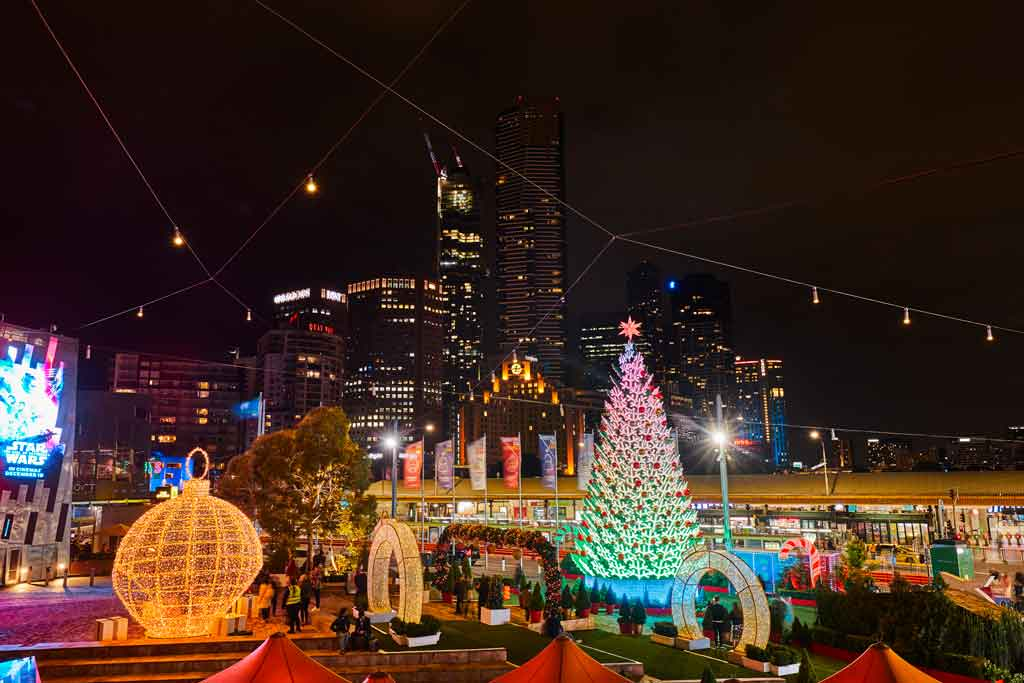 A large glowing Christmas tree and other decorations in an open city square