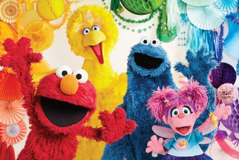 Shot of Sesame Street Elmo character, Cookie monster and Big Bird smiling cheerily at the camera