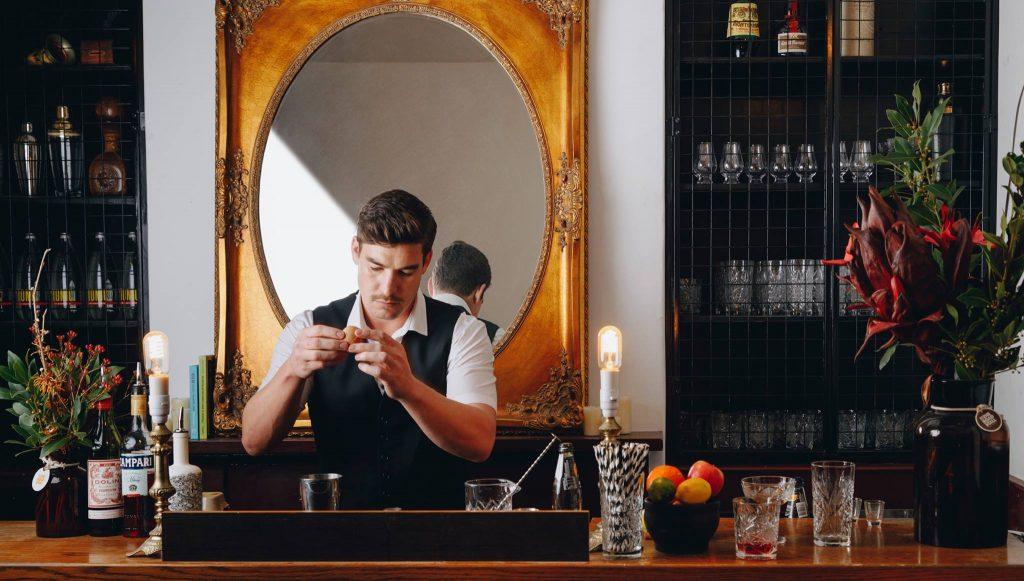 A man behind a bar shaking a martini