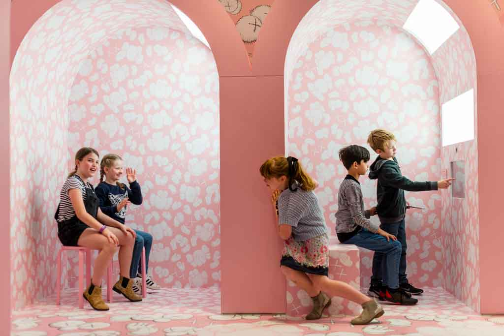 Five kids playing in a pastel pink corridor