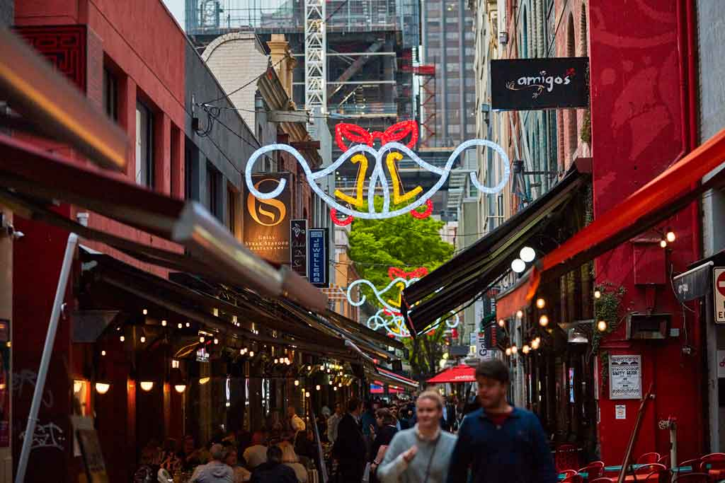 A city laneway with bright Christmas decorations hung above it