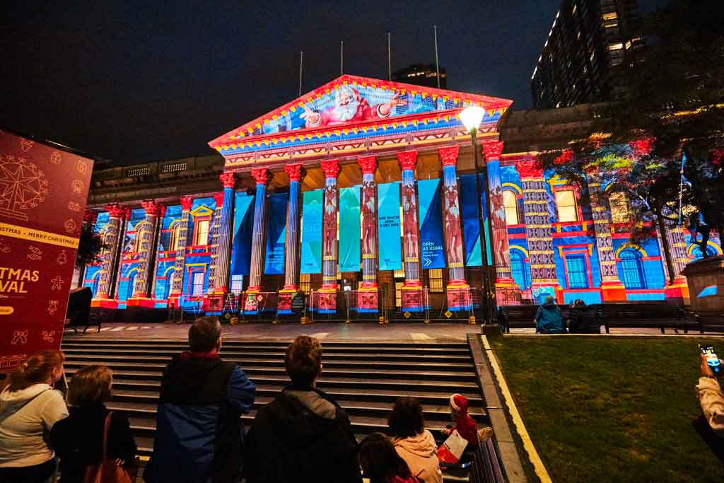 An old building with colourful projections on it at night