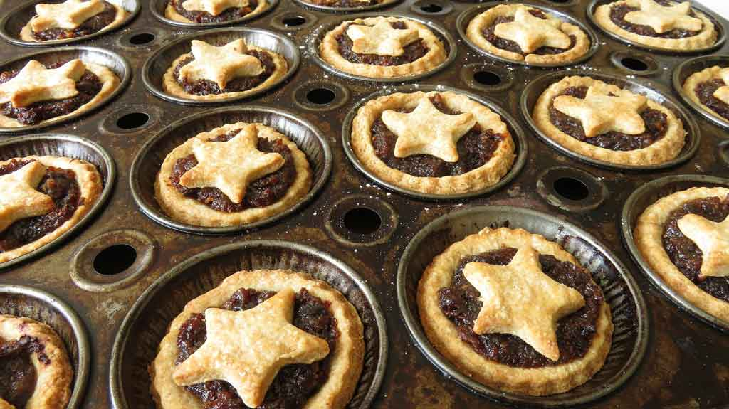 Fruit mince pies in a tray topped with a shortbread crust shaped like a star