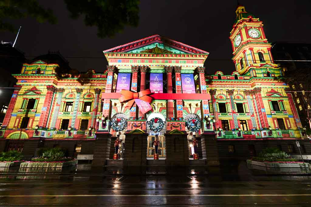 A large old building with colourful projections and Christmas decorations