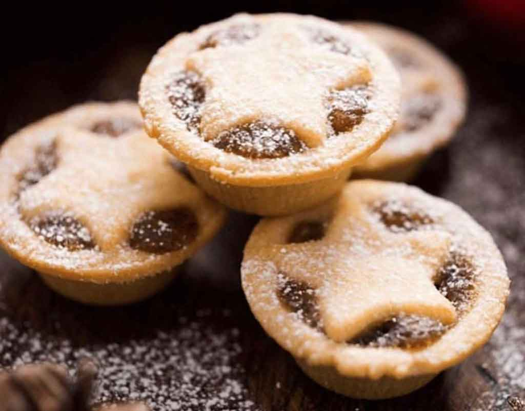 Fruit mince pies on a wooden board
