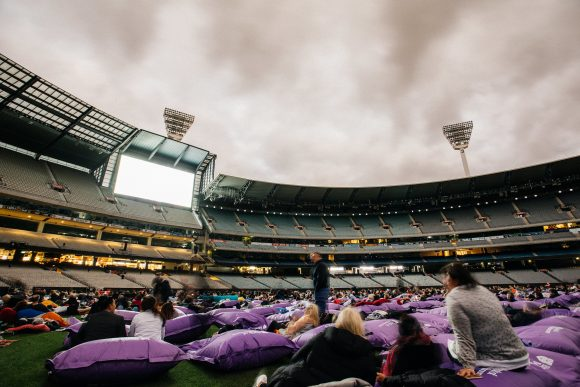 A crowd of people lying with their heads on inflatable pillows and watching a movie at an outdoor stadium