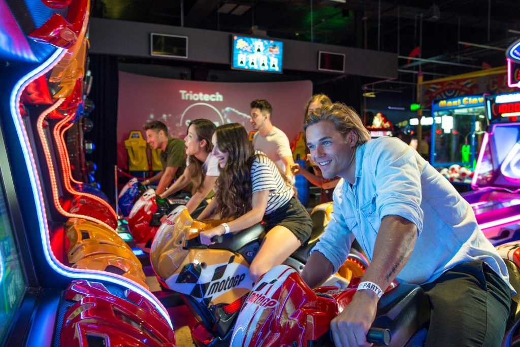 Six people playing motorbike riding arcade games at video game arcade