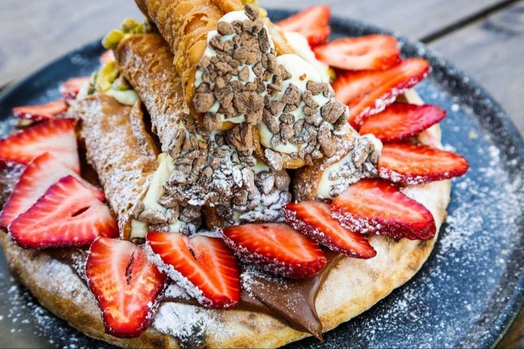 A pizza base covered in Nutella, cannolli and strawberries