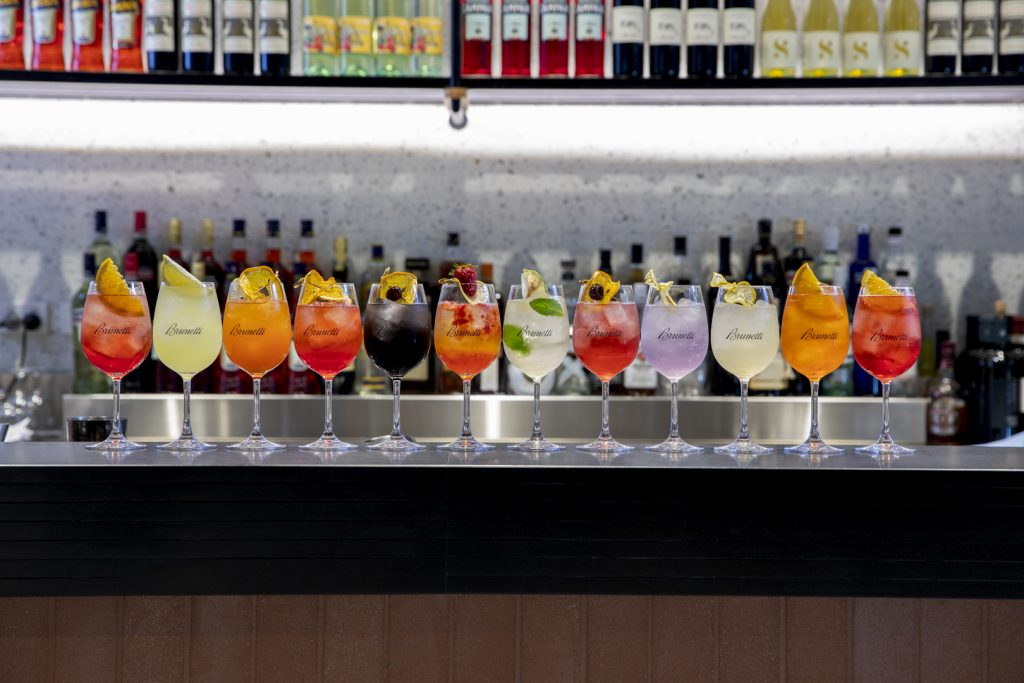 Twelve drinks lined up on top of a bar, each a different colour