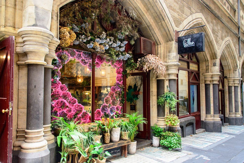 Stone facade of a florist with roses window display and pot plants